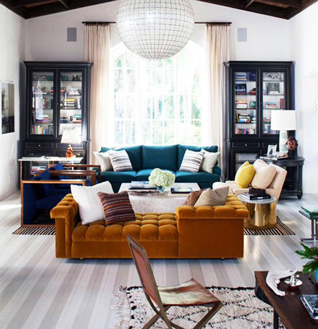 living room: painted wood floors, bold couches, double bookshelves